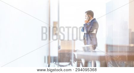 Businessman Talking On A Mobile Phone In Corporate Office While Looking Through Window.