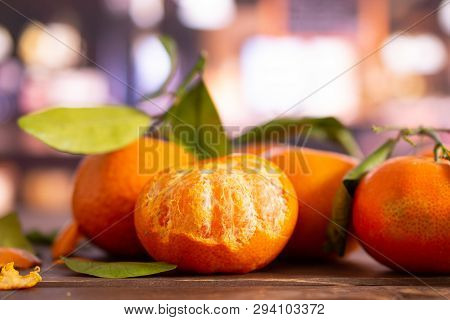 Group Of Four Whole Fresh Orange Mandarine With Green Leaves One Fruit Is Half Peeled In A Restauran
