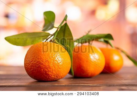 Group Of Three Whole Fresh Orange Mandarine One By One With Green Leaves In A Rustic Kitchen