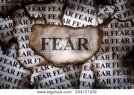 Burnt Fear. Burnt Pieces Of Paper With The Word Fear. Close-up.