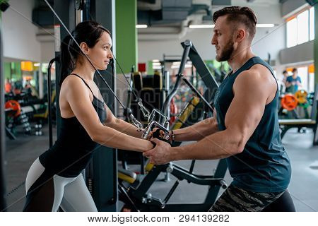Fitness Girl Lifting Dumbbell In Morning With Assistance Of Her Personal Trainer At Public Gym. Conc