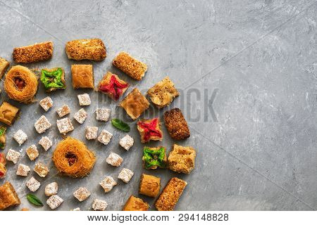 A variety of Middle Eastern sweets on a gray background. Arab dessert, baklava, lokum,cookies. Top view, flat lay, copy space poster