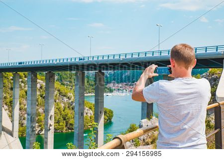 Skradin, Croatia - July 15, 2018: Man Taking Picture Of His Phone Of Bay With Bridge. Copy Space