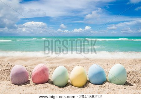Happy Easter Background With Eggs On The Sandy Beach Near Ocean.
