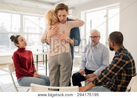 Young friendly man supporting mature blonde female while giving her hug at psychological therapy session