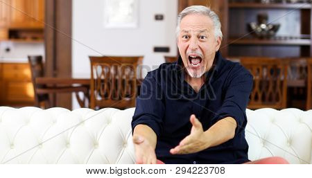 Senor guy watching sports in tv and shouting