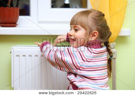 Girl Warm One's Hands Near Radiator