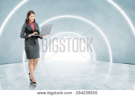 Side View Of Asian Asian Business Woman Holding Laptop With His Hand While Walking On The Office Cor