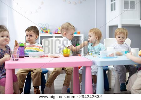 Kids Group Have Lunch In Kindergarten. Cute Child Boy Sharing His Food To Little Girl