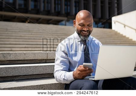 African businessman working on laptop outside a building. Happy black man sitting on stairs working on computer while checking message on phone. Smiling entrepreneur work on project with copy space.