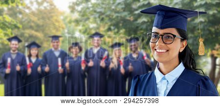 education, graduation and people concept - happy female graduate student in mortarboard and bachelor gown over group of classmates in summer park background