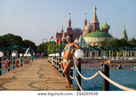 Girl In A Swimsuit On The Pier On The Background Of The Hotel. Girl Posing On The Wooden Pier On The