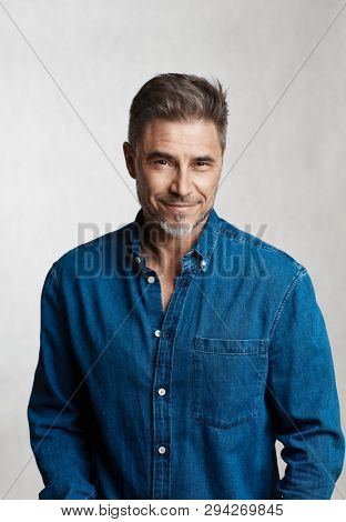 Happy older man in casual jeans shirt smiling isolated on white background.