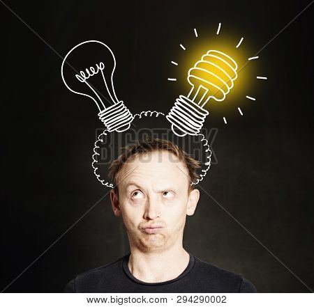Brainstorm. Man With Two Light Bulb On Blackboard Background. Brainstorming And Idea Concept
