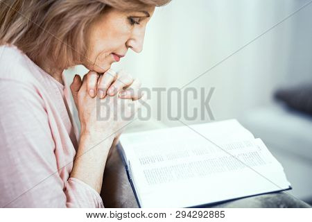 Peaceful Mature Woman Reads A Bible And Prays. Beautiful Woman Touches Her Chin With Clasped Hands W