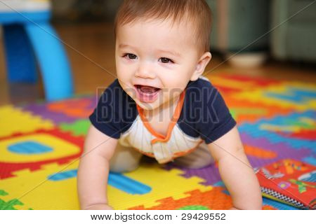 A cute young boy baby playing inside home with colorful toys