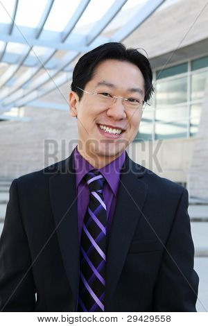 A handsome Chinese business man smiling at the office