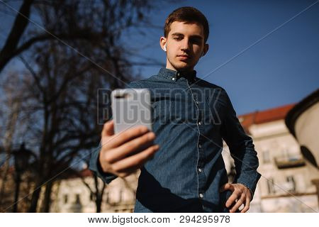 Buttom View Of Man Using A Phone. Young Blogger Texing A Message For Folowers