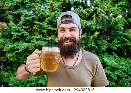 Creative young brewer. Craft beer is young, urban and fashionable. Distinct beer culture. Hipster brutal bearded man hold mug cold fresh beer. Man enjoying beer in summer. Alcohol and bar concept poster