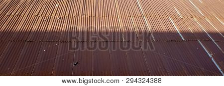 Old Rust-covered Brown Tin Roof Top, Made Of Corrugated Metal Sheets, Partly Covered By Shade.