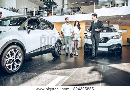 Sales Manager Helping Young Couple To Choose A New Car In Modern Car Showroom.