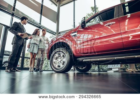 Buying Their First Car Together. Bottom View Of Young Car Salesman Standing At The Dealership Tellin