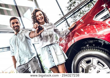 Key To Your Perfect Ride. Young Beautiful Couple Holding Car Key And Looking At Camera With Smile Wh