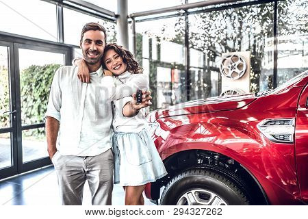 Happy Young Lovely Couple In Casual Wear Hugging While Buying First New Family Car Together In Deale