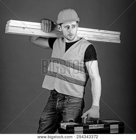 Woodworking Concept. Carpenter, Woodworker, Labourer, Builder On Calm Face Carries Wooden Beams On S