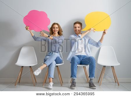 Beautiful young couple with cartoon speech on wall background. People and speaking bubbles.