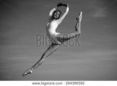 Practicing The Art Of Classical Ballet. Young Ballerina Jumping On Blue Sky. Pretty Woman In Dance W