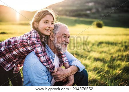 A Small Girl With Grandfather Outside In Spring Nature, Relaxing On The Grass.