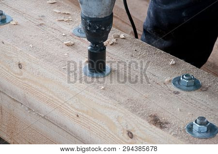 The Process Of Closing Bolts On A Wooden Beam. Fastening Wooden Beams Among Themselves.