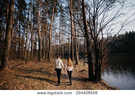Beautiful Portrait Of A Pregnant Woman And Her Husband. They Are Standing Near The Trees Back To The