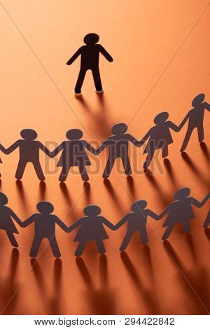 Paper human figure standing in front of paper people holding hands on red surface. Bulling, conflict, segregation concept.