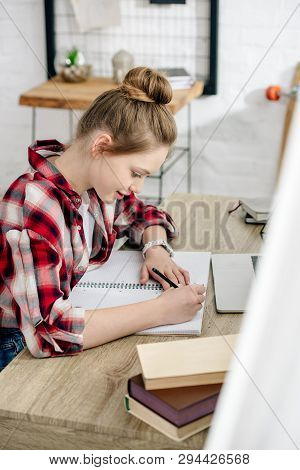 Teenager In Checkered Shirt Writing In Notebook While Doing Homework