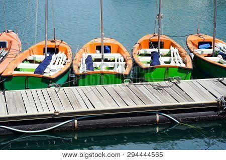Small Training Sailing Boats At The Pier. Several Small Tourist Boats Standing In Row At A Pier On A