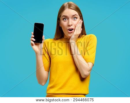 Stupefied Girl Opens Eyes And Mouth Widely, Holds A Phone. Photo Of Young Girl With Surprised Expres