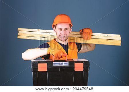 Man In Helmet, Hard Hat Holds Toolbox And Wooden Beams, Grey Background. Carpenter, Labourer, Builde