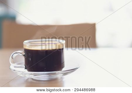 Closeup Glass Of Hot Americano Coffee On Wood Table With Smoke, Selective Focus, Vintage Tone