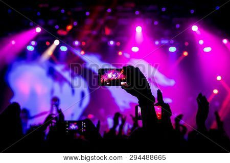Smartphone In Hand At A Concert, Purple Light From Stage