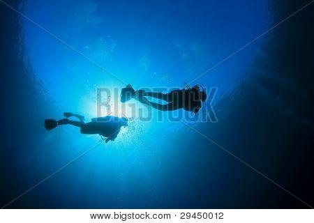 Two Scuba Divers in blue ocean with sunburst
