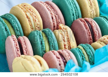 Assortment Of Fresh French Macarons Packaged In A Pretty Blue Paper With Blurred  Background..