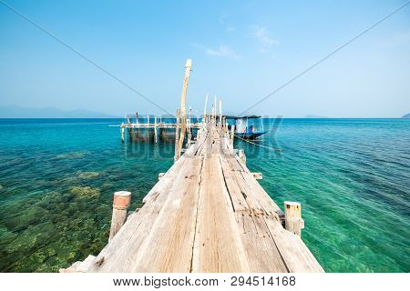 Seascape With Pier And Small Fishing Boat. Beautiful View From The Wooden Pier On The Azure Sea Coas