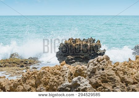 Beach Rocks, Sea Water Hitting The Rocks On The Bay. Pointed Spongy Rocks. Set Of Rocks Near The Sea