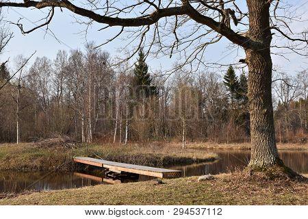 Small Wooden Bridge Crossing A Pond In An Idyllic Landscape