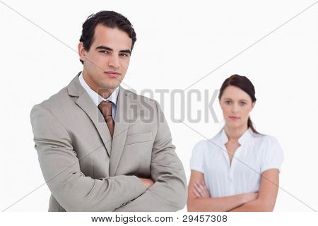 Salesman with arms crossed and colleague behind him against a white background