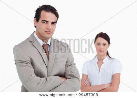 Verkäufer mit Arme verschränkt und Kollegen hinter ihm vor einem weißen Hintergrund