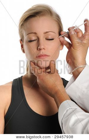 Portrait of young woman receiving injection of neurotoxin isolated over white background