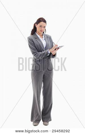 geschäftsfrau schreiben auf eine Zwischenablage against white background